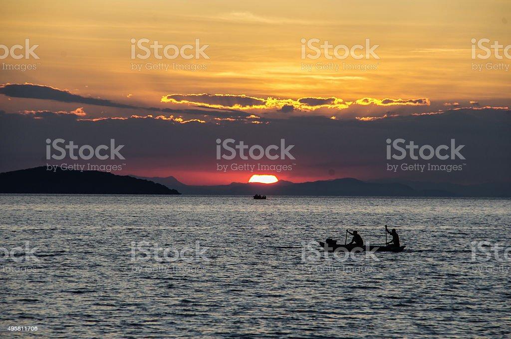African Fishermen paddling infront of sunset stock photo