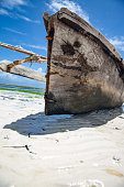 African Fishing sailboat made from Mango tree wood on Zanzibar beach during low tide