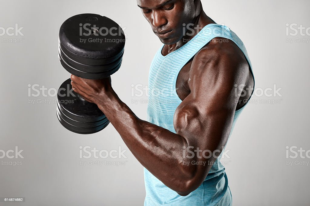 African fitness model exercising with heavy dumbbells stock photo
