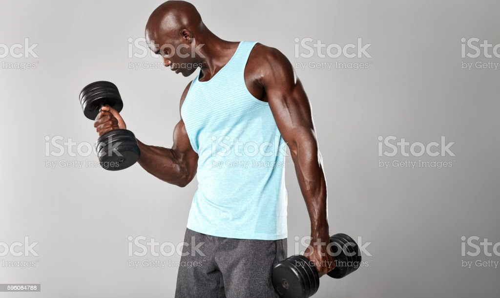 African fitness model working out with dumbbells stock photo