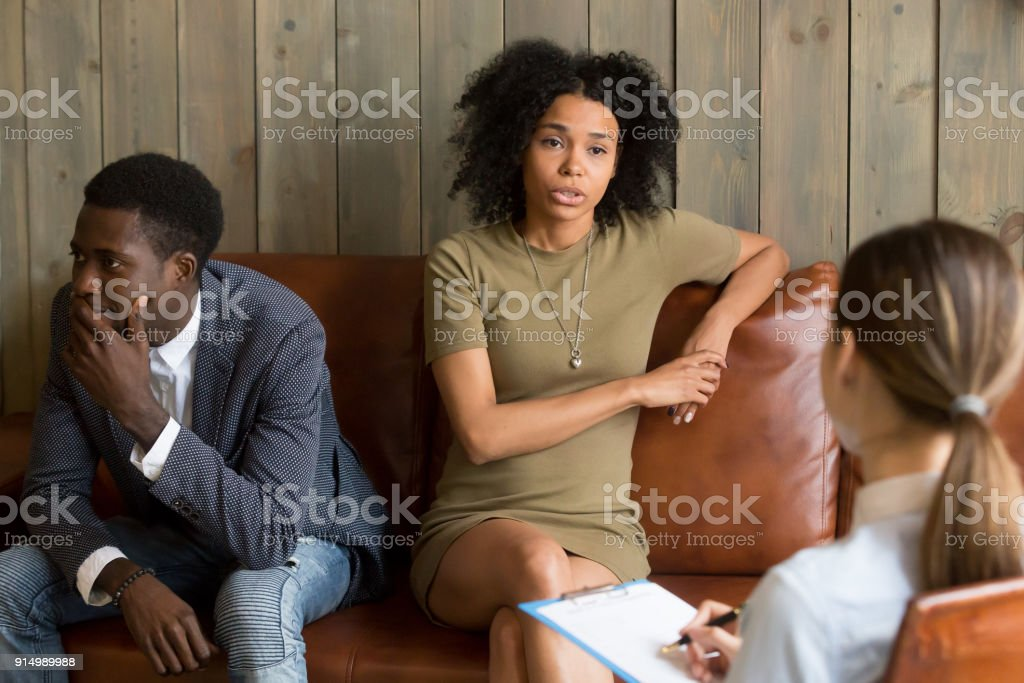 African frustrated wife talking to psychologist, family marriage therapy session stock photo