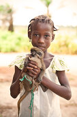 An African girl holding a small monkey.