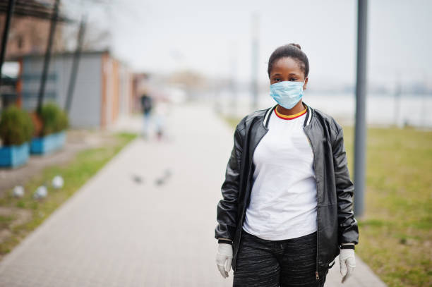 African girl at park wearing medical masks protect from infections and diseases coronavirus virus quarantine. stock photo