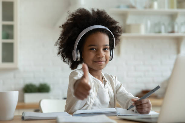 African girl in headphones enjoy showing thumbs up e-learning stock photo
