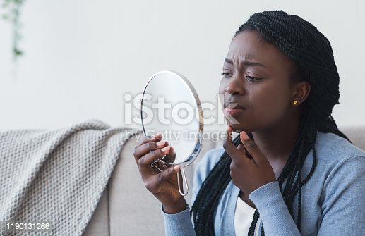 istock African Girl Looking In Round Mirror and Touching Her Chin 1190131266