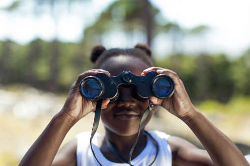 African girl looking though a binoculars