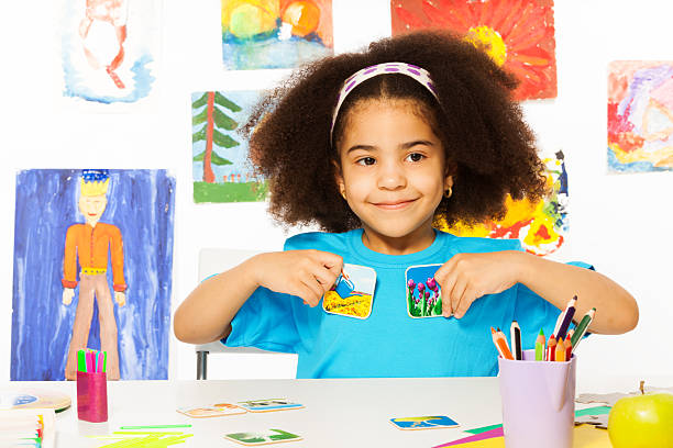 African girl plays developmental game, holds cards stock photo