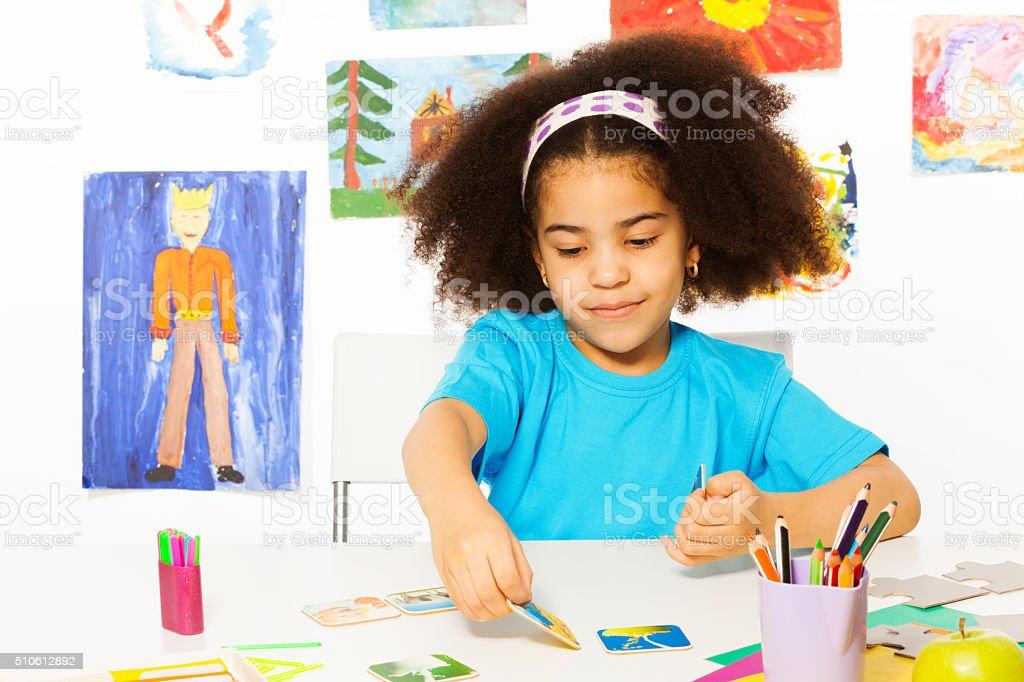 African girl plays developmental game putting card stock photo