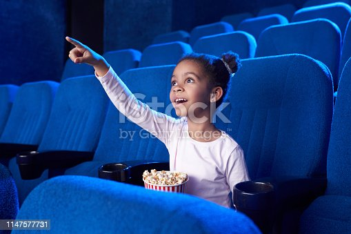 istock African girl poiniting with finger at screen in cinema. 1147577731