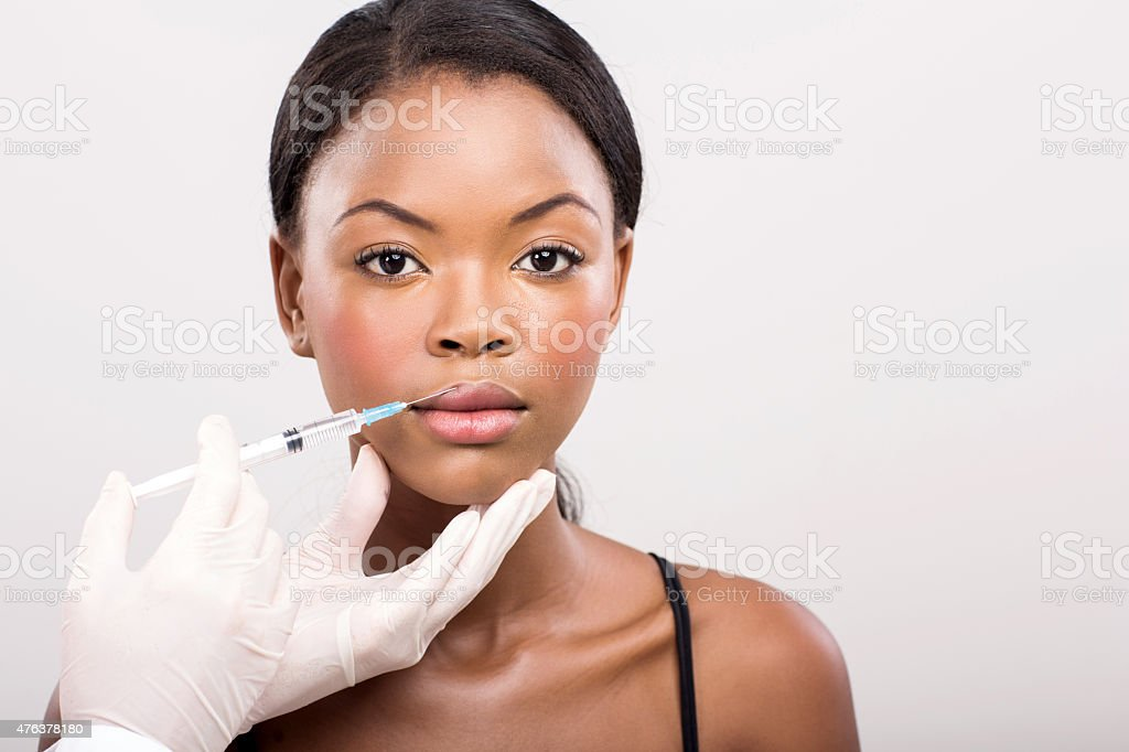 african girl receiving cosmetic injection on her lips stock photo