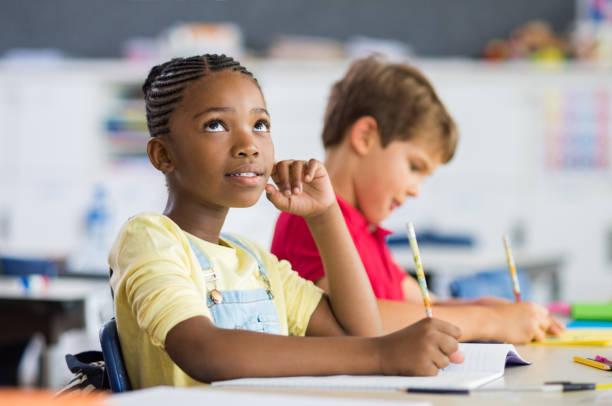 クラスで考えてアフリカの女の子 - 作文の授業 ストックフォトと画像