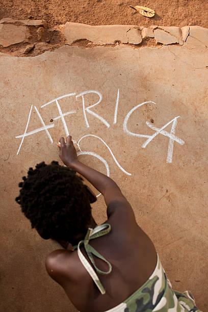 afrykańska dziewczyna pisania na podłodze - back to school zdjęcia i obrazy z banku zdjęć