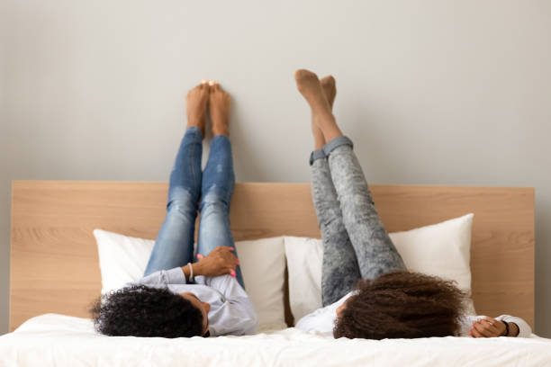 African girlfriends lying chatting on bed raised legs up stock photo