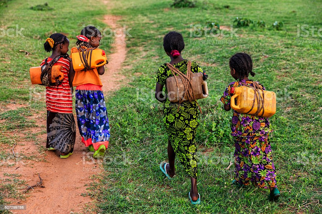 African girls carrying water from the well, Ethiopia, Africa stock photo