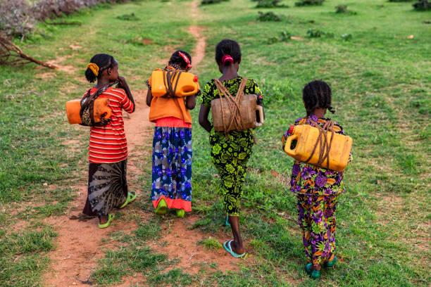 afrikanische mädchen tragen von wasser aus dem brunnen, äthiopien, afrika - was bringt unglück stock-fotos und bilder