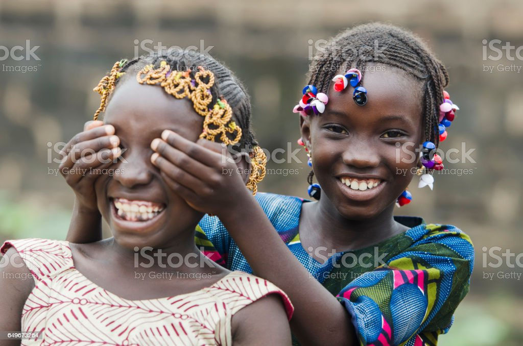 African Girls Playing Peekaboo Outdoors Laughing and Smiling Together (Happiness Symbol) stock photo