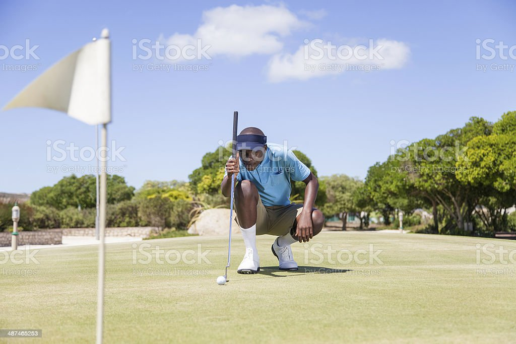 African golfer aiming to make his next putt perfect. stock photo