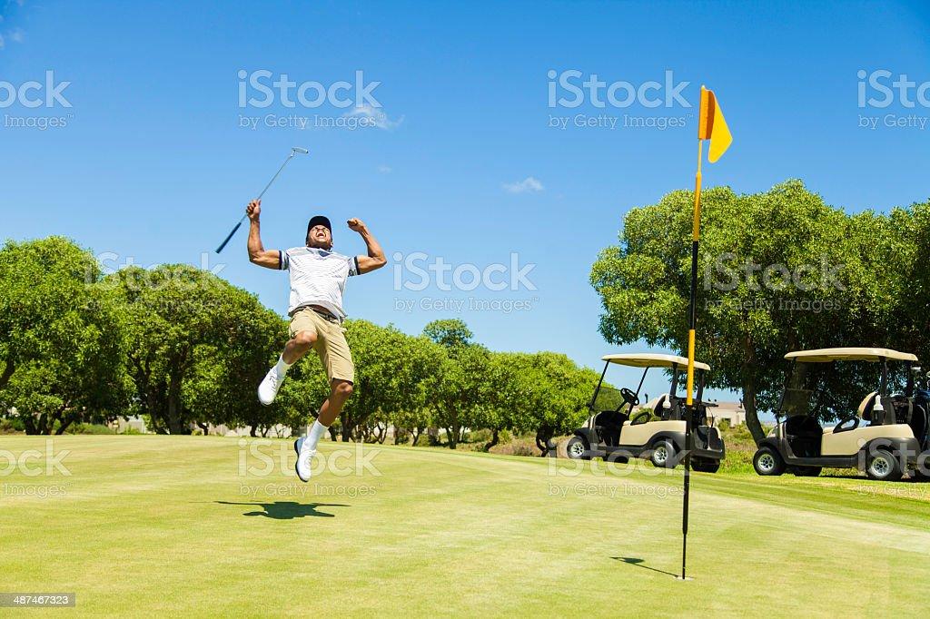African golfer celebrating sinking his putt! stock photo