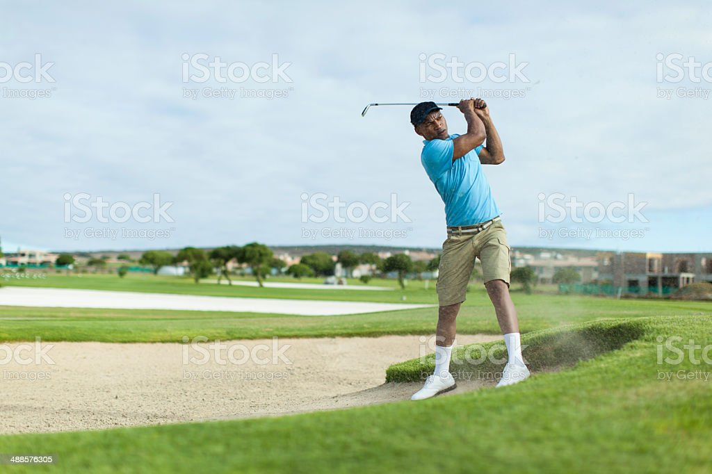 African golfer getting a good shot out of the bunker. stock photo