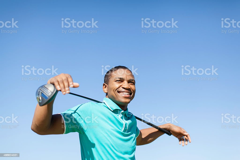 African golfer smiling, holding a golf club over his shoulder. stock photo