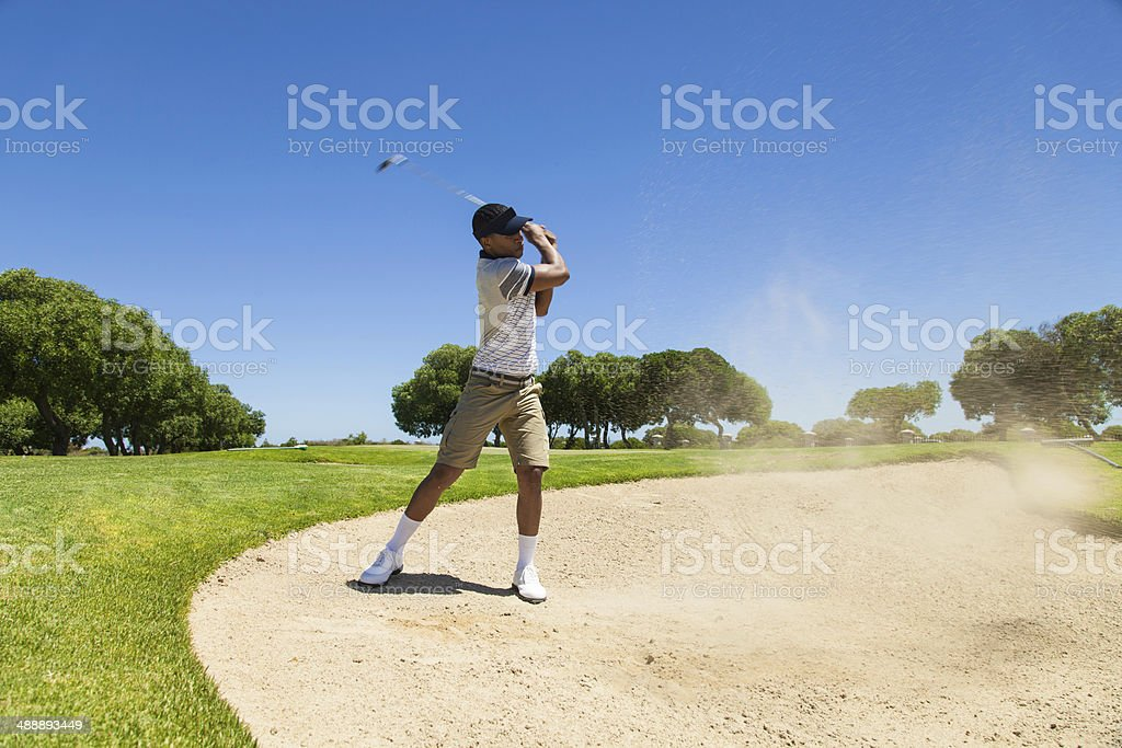African golfer taking a shot in a bunker royalty-free stock photo
