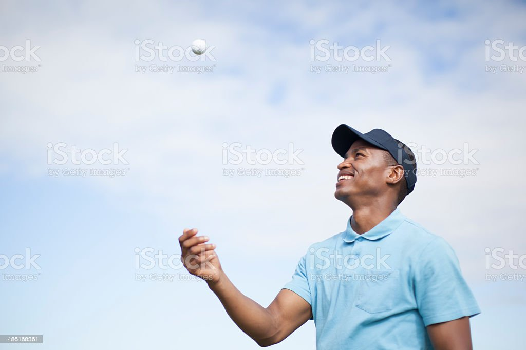 African golfer throwing his golf ball in the sky. stock photo
