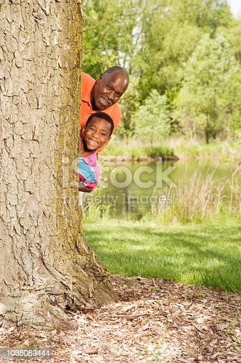 646011750 istock photo African grandfather and grandson peeking out from behind tree in park 1035089444