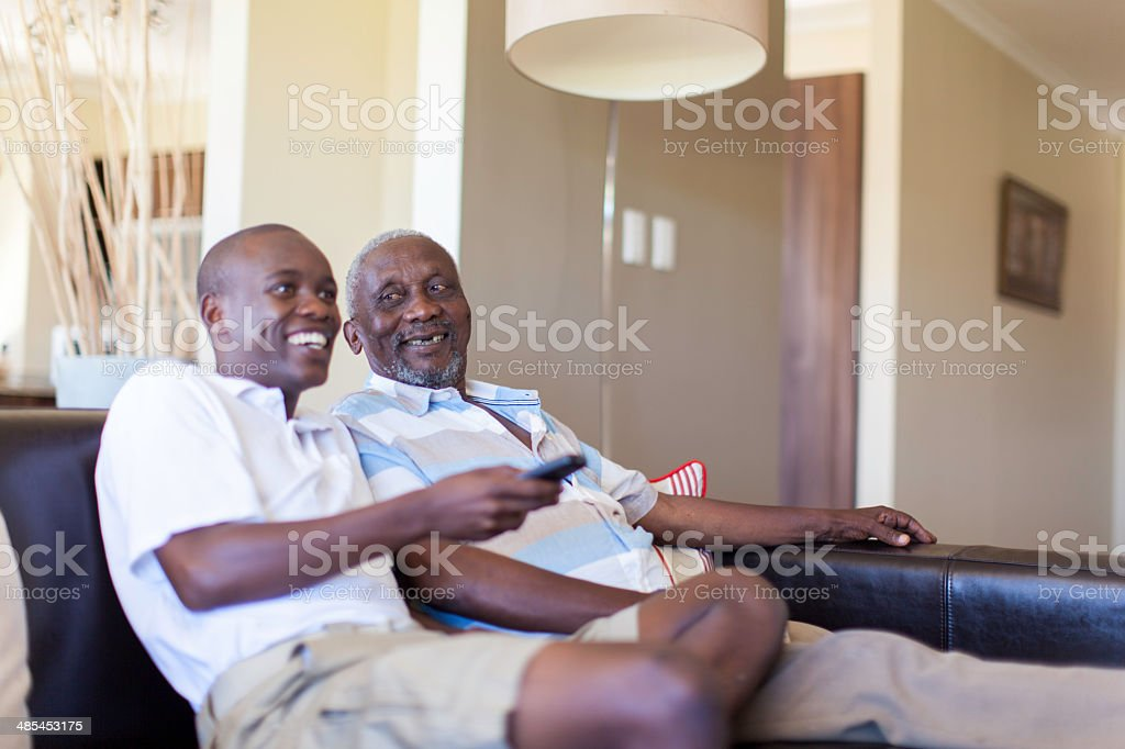 African grandfather and grandson watching television together stock photo