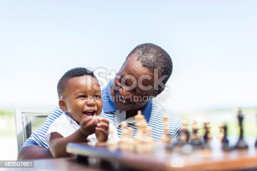 African grandfather sitting down with his grandson on his lap, teaching him how to play chess, having a good laugh together. Langebaan, Western Cape, South Africa