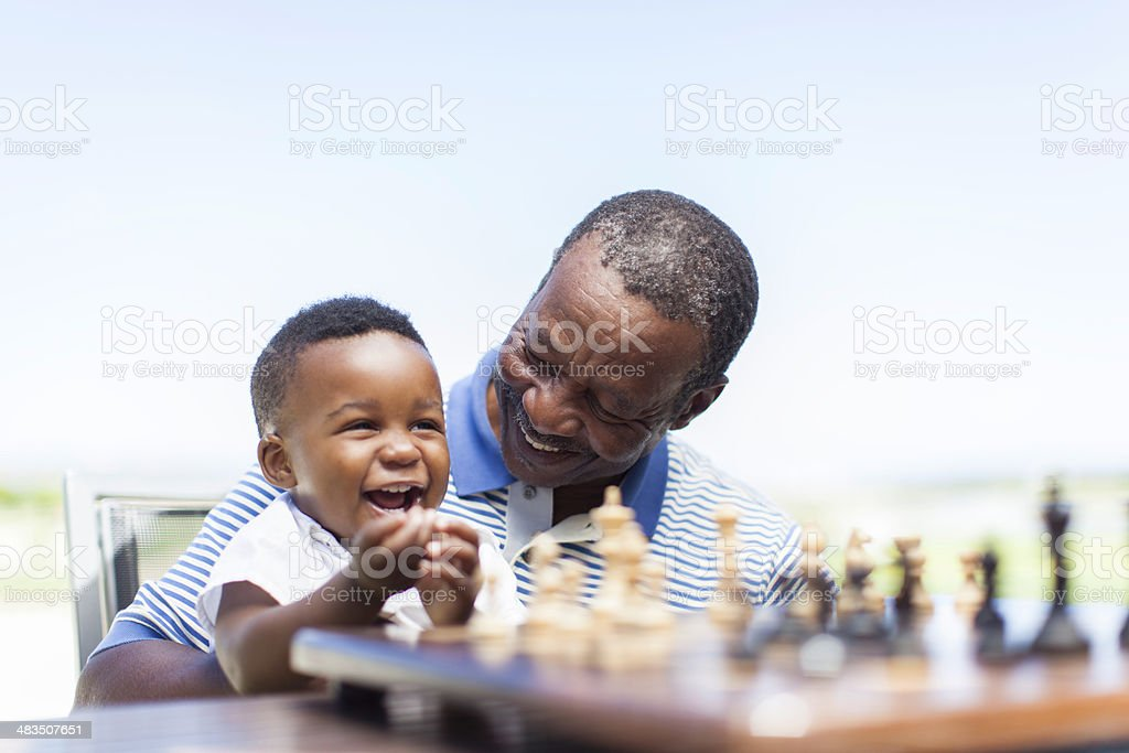 African grandfather playing chess with his grandson stock photo