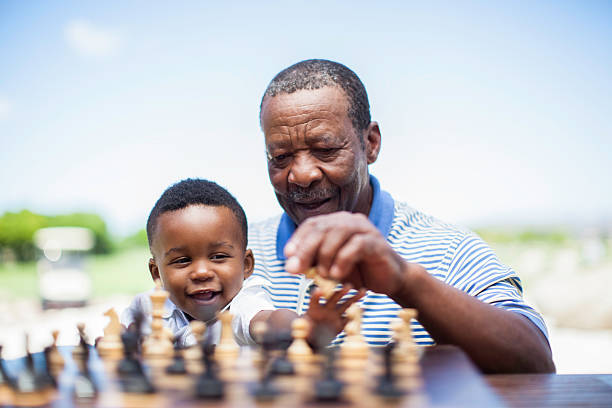 african grandfather playing chess with his grandson - game of life stock photos and pictures