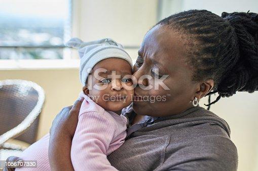 African grandmother kissing her granddaughter.