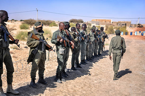 African group of rebel soldiers Bamako, Mail- February 14, 2013: The photo speak about group of african soldiers in Mali who are standing with Kalashnikov in front of them commander during warm afternoon. All men wearing military uniform - camouflage clothes. The climate is arid and very tropical. genocide stock pictures, royalty-free photos & images