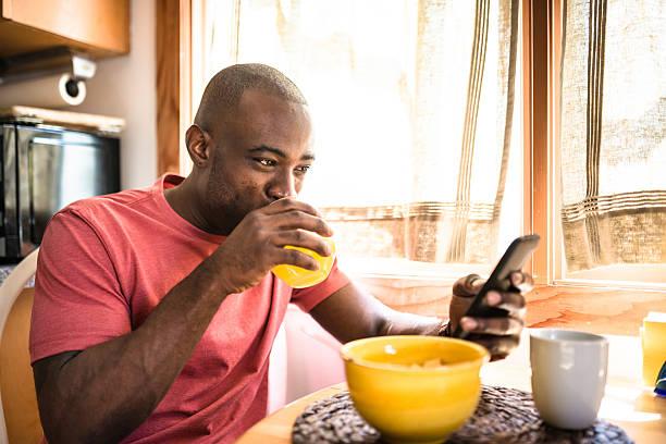 afrikanische mann tun frühstück wie zu hause fühlen. - checking stock-fotos und bilder