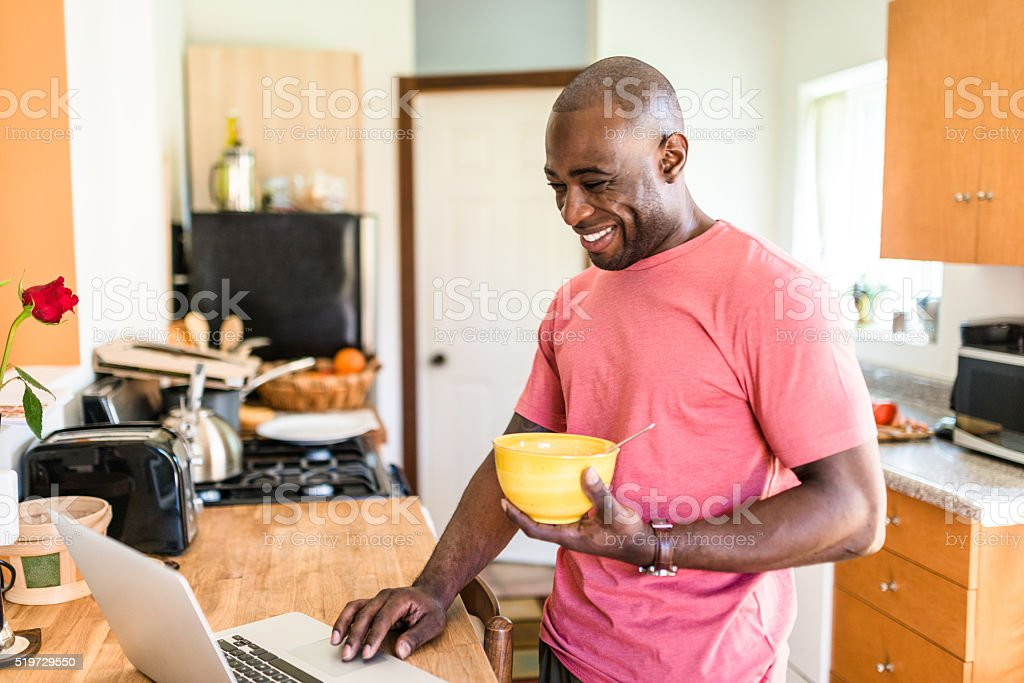 african guy doing the breakfast on the pc stock photo