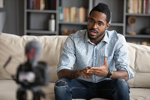istock African guy filming online training webinar using camcorder 1253929844