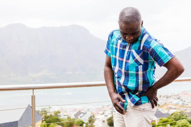 African guy having severe hip pain stock photo