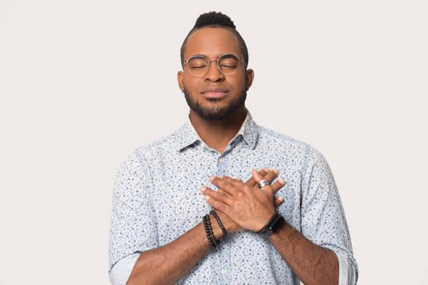 o indivíduo africano prende as mãos na mostra do peito sentimentos sinceros - consciencia negra - fotografias e filmes do acervo