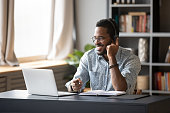 istock African guy learn online wearing headset looking at laptop screen 1253877184