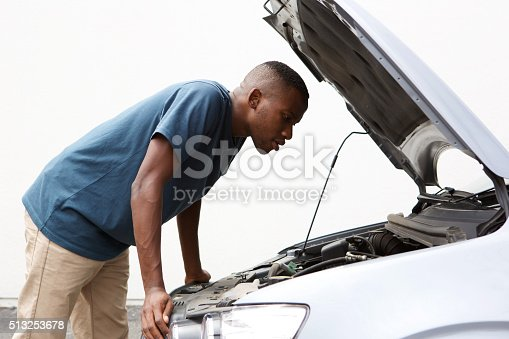 istock African guy looking under hood of broken down car 513253678