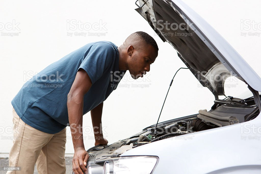 African guy looking under hood of broken down car stock photo