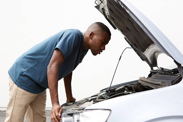 African guy looking under hood of broken down car Side portrait of young african american guy looking under the hood of broken down car vehicle hood stock pictures, royalty-free photos & images