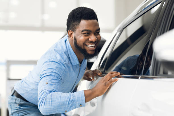 African Guy Touching His New Vehicle In Dealership Showroom stock photo