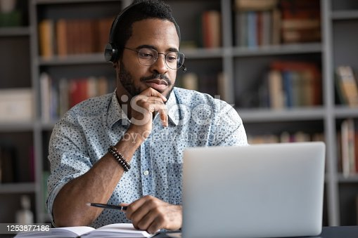 Focused African man wear headphones with microphone looking at laptop screen listens audio lesson learn foreign language with tutor makes video call. Student watching webinar, e study on-line concept