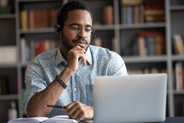 African guy wearing headset learn foreign language using internet websites Focused African man wear headphones with microphone looking at laptop screen listens audio lesson learn foreign language with tutor makes video call. Student watching webinar, e study on-line concept adult stock pictures, royalty-free photos & images