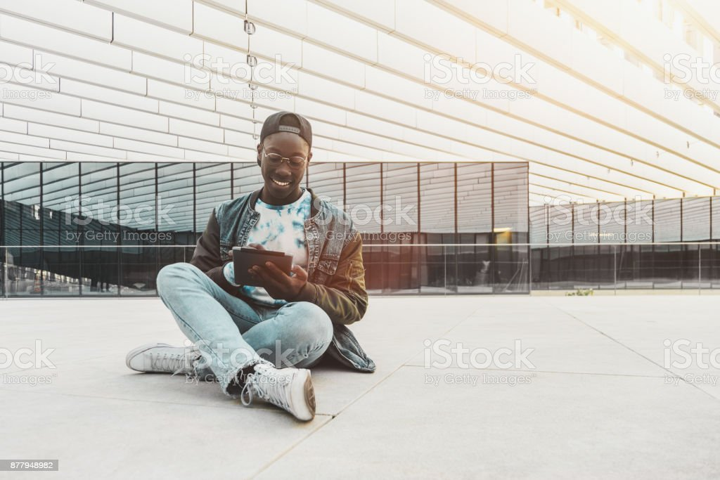 African guy with digital pad outdoor stock photo