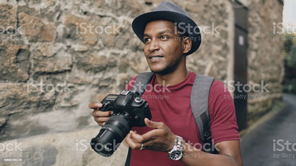 African happy tourist taking photo on his dslr camera. Young man travelling in Europe stock photo