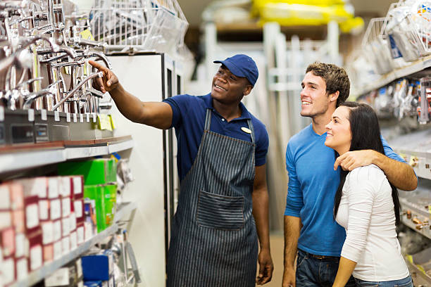 african hardware store assistant helping customers friendly african hardware store assistant helping young couple choosing taps sales clerk stock pictures, royalty-free photos & images
