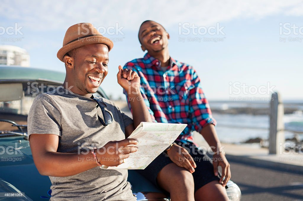Two African hipster friends reading a map by the sea on holiday. Cape...