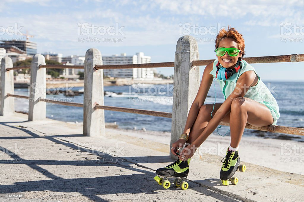 African hipster girl putting on roller blades by the sea stock photo